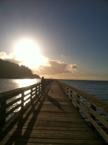 sun breaking thru on pier